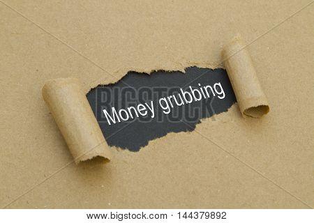 money grubbing word written under torn paper.