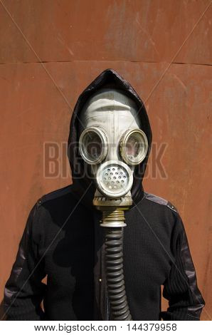 Man is in a gas mask and hood on rusty background