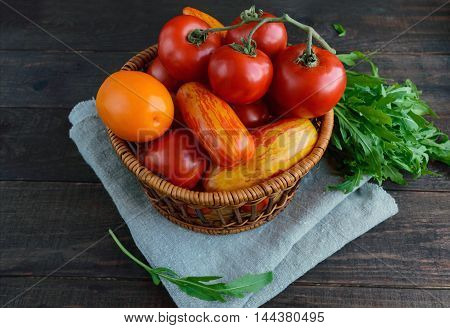 Basket with tomatoes of different varieties and arugula sheaf on dark wooden background.