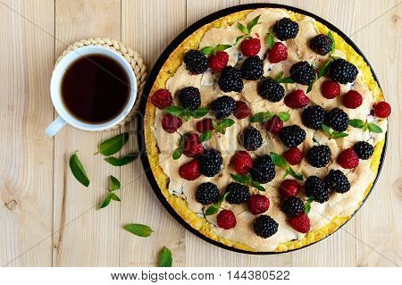 Pie (Tart) with fresh blackberries and raspberries air meringue decorative mint and cup of tea