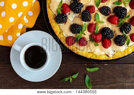 Pie (Tart) with fresh blackberries and raspberries air meringue decorative mint and cup of coffee