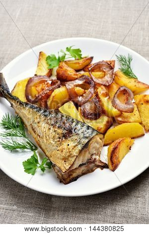 Fried mackerel fish and potato wedges on plate