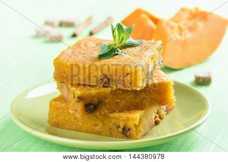 Sliced pumpkin pie with nuts on plate