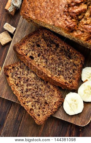 Sliced banana bread on wooden board top view
