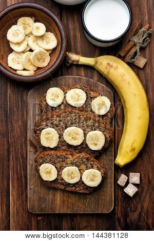 Slices of sweet banana bread on wooden board top view