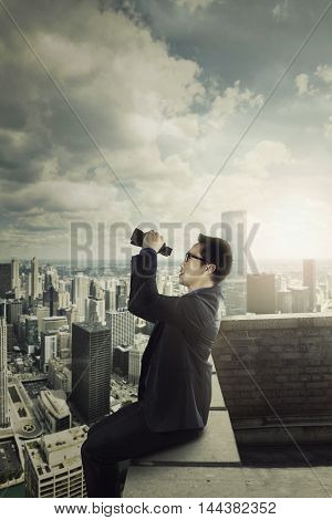 Young businessman sitting on the building roof while looking at the sky with a binocular