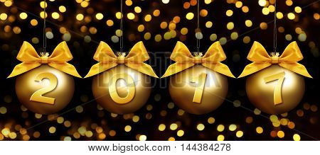 christmas balls and 2017 text with golden satin ribbon bow on blurred gold lights background