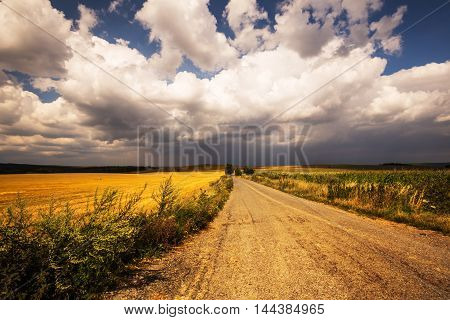 Dense clouds over fields and road. Moravian landscape Premyslovice.