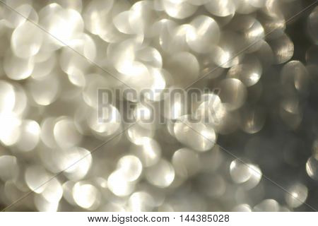 sparkling abstract bokeh defocused blurred background silver color with glitter circles and no people