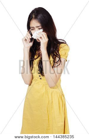 Portrait of a pretty teenage girl talking on the phone while crying in the studio isolated on white background