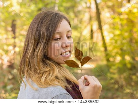 Happy Woman Holding Autumn Leaf In Park