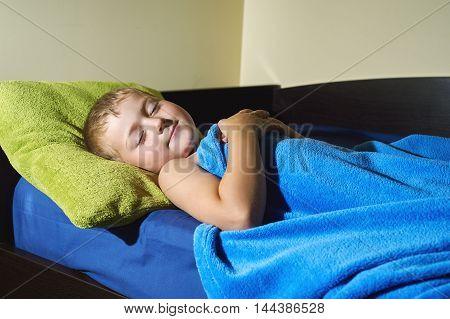 the boy was sleeping .tired boy sleeping in bed