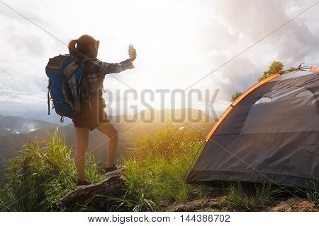 A woman use smartphone take a photo sunrise in Camp on the mountains.