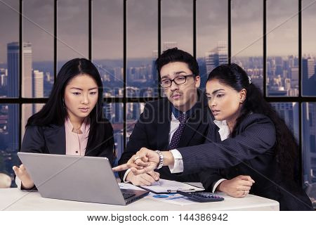 Portrait of three multi ethnic entrepreneurs discussing business plan and strategy with laptop in the office