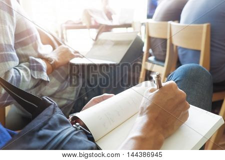 Hipster man Handwriting hand writes a pen in a notebook in class room.