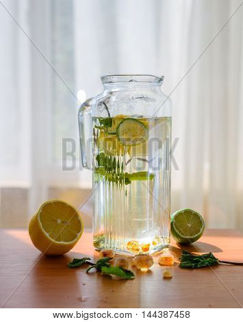 Homemade lemonade with scattered citrus fruits and other ingredients. refresh in summer day
