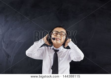 Male primary school student wearing headphones while wearing uniform in the class