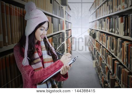 Female high school student wearing winter clothes while writing on the clipboard in the library