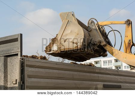 Shovel tilts earth in a low loader