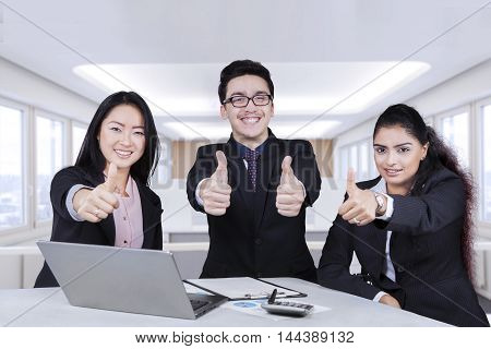 Group of multiethnic entrepreneurs showing thumbs up with laptop on the table shot in the office