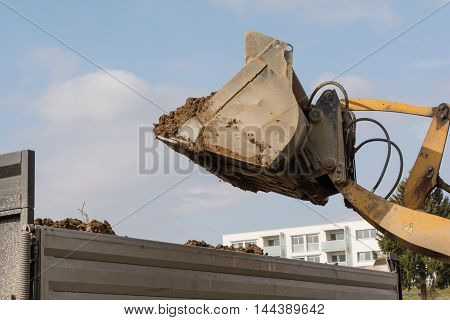 Dump truck shoveling earth from construction loaders - Closeup