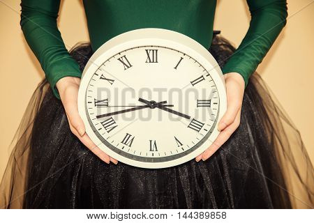 a woman in a skirt holding a clock