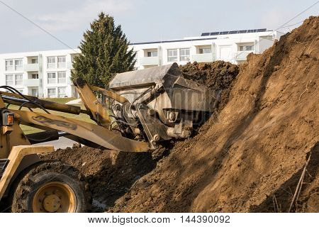 Shovels shoveling of soil heap on a construction site earth away