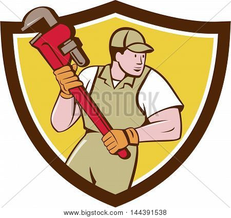 Illustration of a plumber holding giant pipe wrench looking to the side viewed from front set inside shield crest on isolated background done in cartoon style.