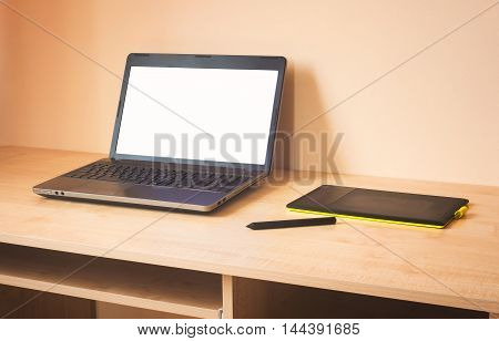 laptop and graphics tablet on wooden table