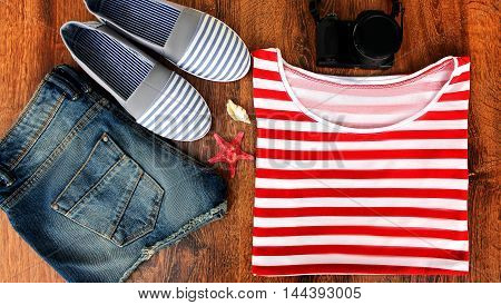 Set clothes for going to sea: jeans shorts, a striped shirt and striped sneakers, photocamera, shells, a top view of a wooden background.