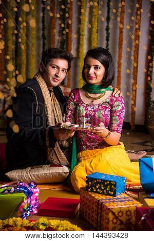 Portrait of indian or Maharashtrian couple holding a puja thali, sitting with gift boxes and rangoli on floor on the occassion of diwali festival