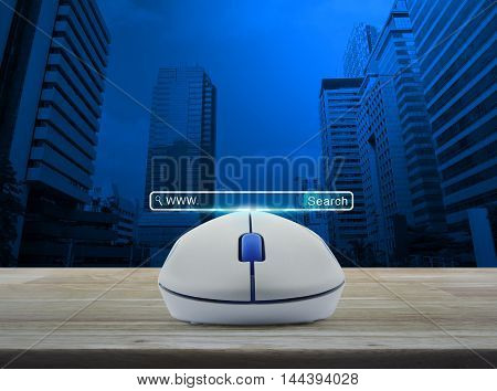Wireless computer mouse with search www button on wooden table over city tower Searching system and internet concept