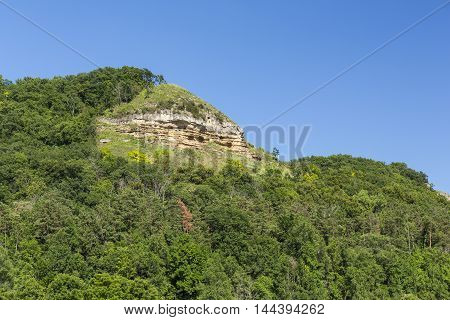 A scenic hill with a cliff in summer.