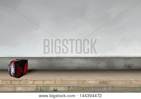 Red suitcase on road