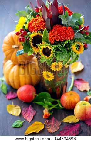 Autumn still life.Autumn bouquet of flowers with pumpkins ,apple and leaves .