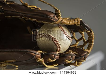 Close-up of a used baseball ball inside brown leather baseball glove on plain grey background.
