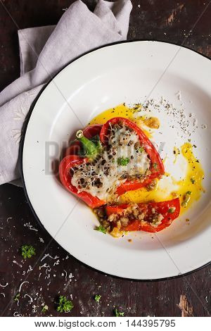 Stuffed red bell pepper with minced meat, rice, carrot, onion, parmesan cheese, parsley in a plate on a wooden table, selective focus