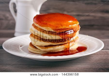 Honey over stack of pancakes on plate