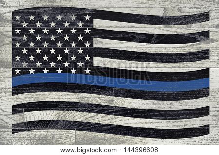 A police law enforcement flag with blue stripe over a white washed wooden floor.