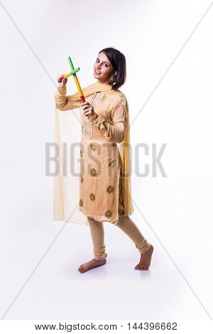 Indian beautiful young girl playing dandiya with garba sticks on Indian Festival Navratri, isolated on white background
