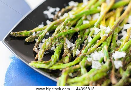 Roasted asparagus and coarse salt on the plate, a traditional snack in Spain, delicious and healthy diet meal.