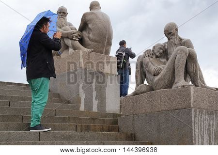 OSLO, NORWAY - JULY 1, 2016: Visitors take pictures in the memory of sculptures of the bridge in the Vigeland Sculpture Park.