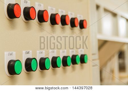 Red stop and green start buttons on control panel of automatic machine control.