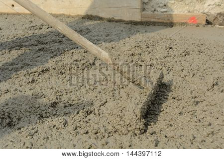 Concrete mixture is smoothed on construction site with iron rakes