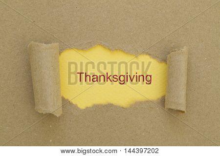 Thanksgiving word written under torn paper .