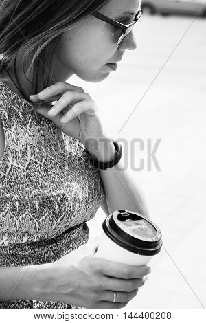 Side view of young woman with coffee to go walking and looking down.Black and white.
