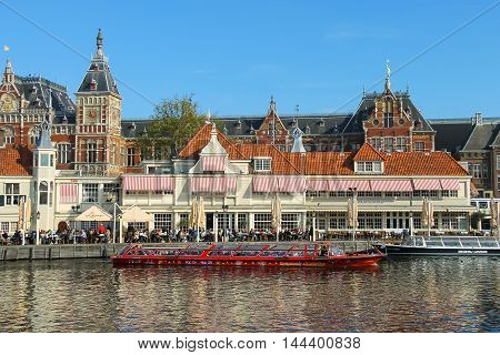Amsterdam the Netherlands -October 03 2015: Tourist boats on the canal of Amsterdam. View of Amsterdam Central Station from water canal