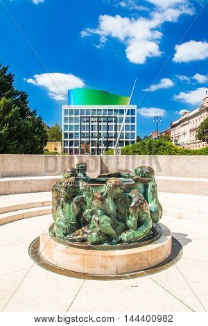 ZAGREB, CROATIA - AUGUST 13th, 2016, Well of Life, sculpture made by Croatian sculpturer Ivan Mestrovic with the new modern building of Croatian Music Academy in background