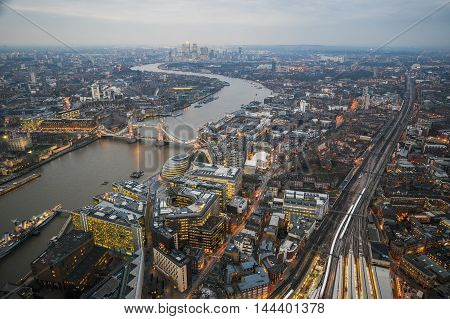 London England - Aerial Skyline view of London with the amazing Tower Bridge the Tower of London and skyscrapers of Canary Wharf at dusk