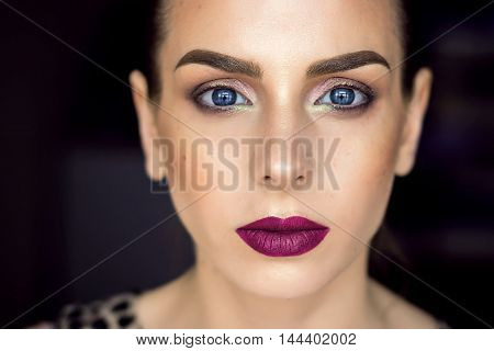 Beautiful girl with perfect skin and wine lips. Picture taken in the studio. Blue eyes and graphic eyebrows.